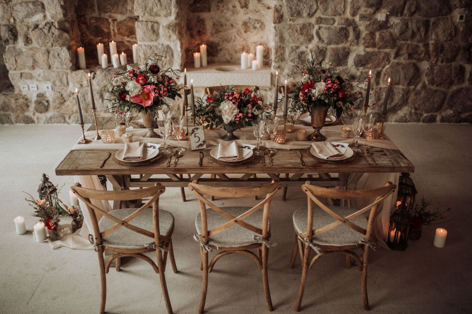 This image is a close up of a reception set up. The details are gold and rose gold. The runner on the wooden table and the main plate are both a very light shade of pink.