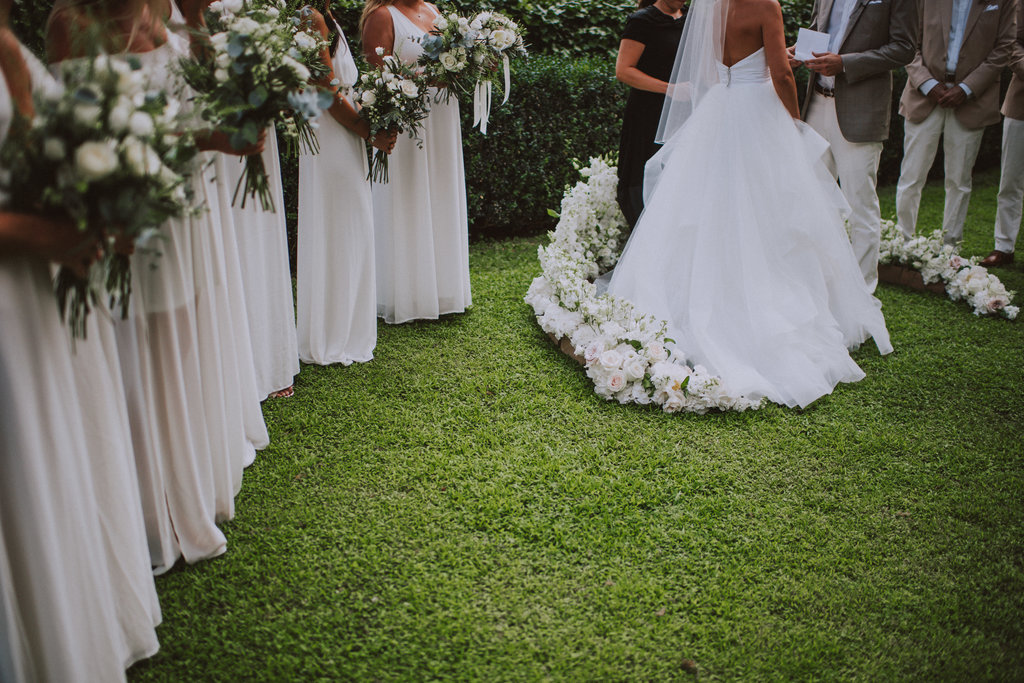 Dubrovnik romantic wedding ceremony set up at hotel Villa Argentina garden. There's a floor flower arch made up of white flowers and the bride and groom are in the middle of it. The guests are watching the ceremony from wooden chairs. There's grass on the floor and beautiful trees all around. Garden ceremony.
