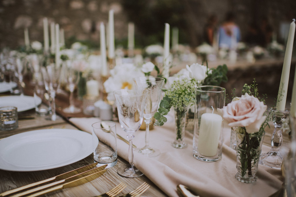 Dubrovnik romantic wedding dinner / reception set up: roses, crystal. It's a close up of the table with plates, golden cutlery and glasses with roses.
