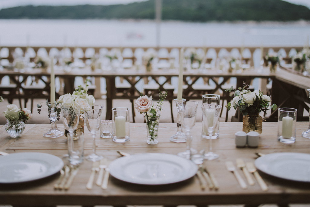 Dubrovnik Villa Argentina wedding reception romantic set up with pink blush roses. The table and chairs are wooden. They are on a beautiful seaside terrace overviewing the island of Lokrum.