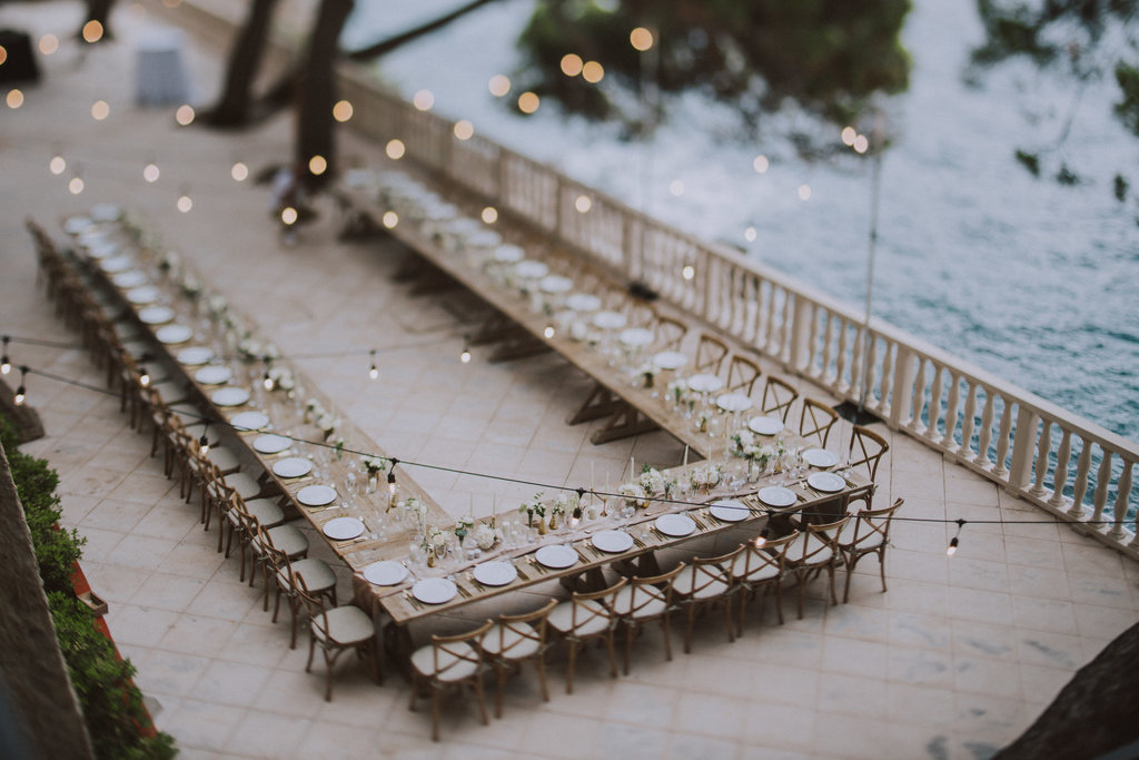 Dubrovnik wedding reception at hotel Villa Argentina terrace overlooking Villa Sheherezade. This photo shows the whole table and chair set up as well as beautiful string lights over them. On one side is the sea and on the other a stone wall with green vines.