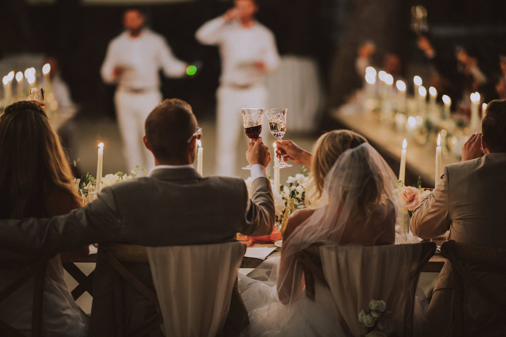 Couple toast at Villa Argentina venue. In this photo it's already dark. The best man is giving his speech. He is standing in the middle of the U-shaped table set up. The guests are listening. The fairy lights are glistening and the candles have been lit. It looks beautiful!