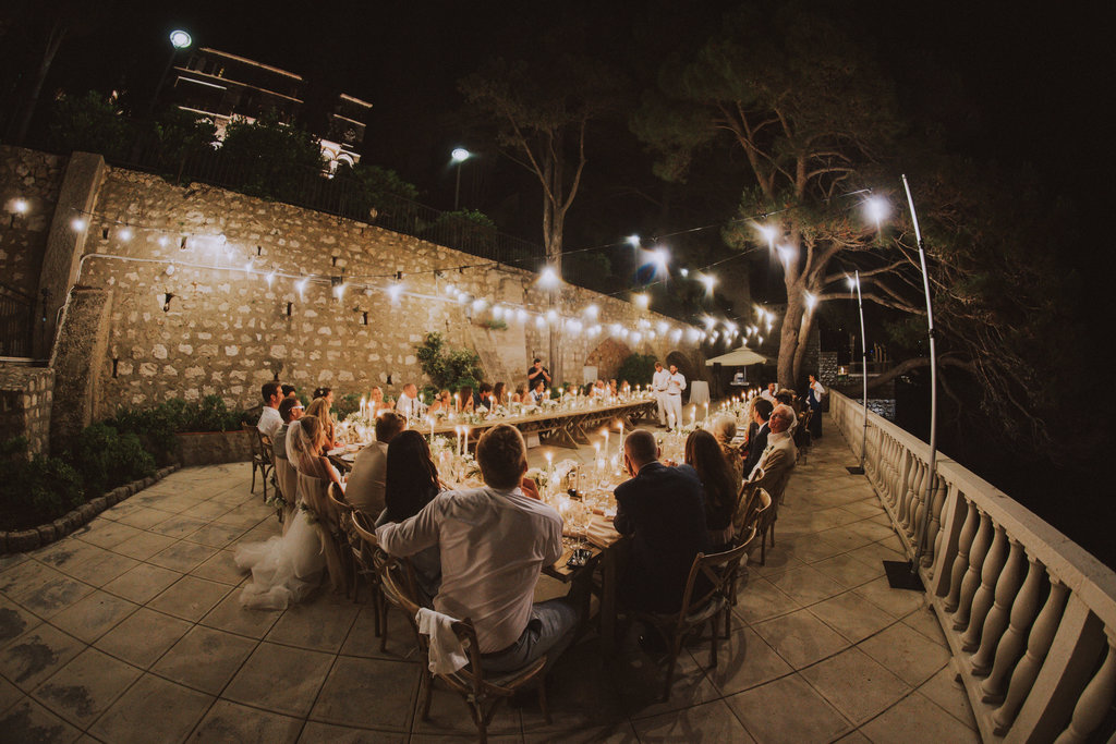 In this photo it's already dark. The best man is giving his speech. He is standing in the middle of the U-shaped table set up. The guests are listening. The fairy lights are glistening and the candles have been lit. It looks beautiful!