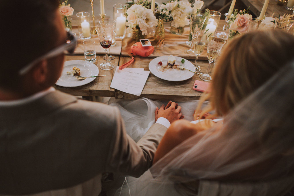 The newlyweds are holding hands. The best man is giving his speech. He is standing in the middle of the U-shaped table set up. The guests are listening. The fairy lights are glistening and the candles have been lit. It looks beautiful!