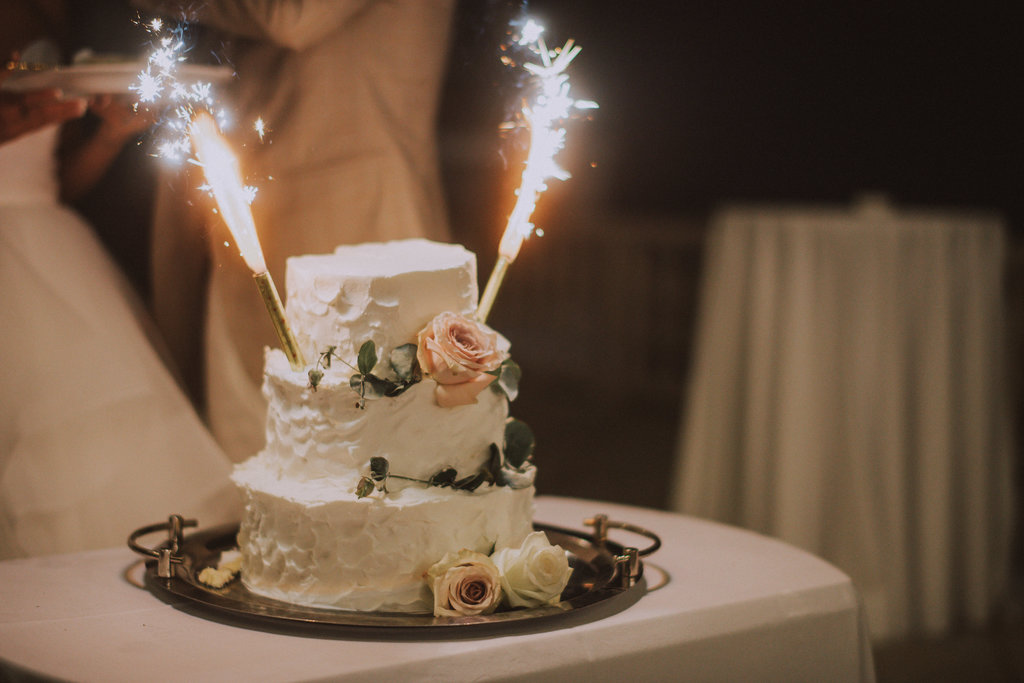The couple is cutting their cake. The cake is mainly white with pastel colored flowers. The groom is wearing a tan suit while the bride is in a simple white wedding dress. She is laughing at someone.