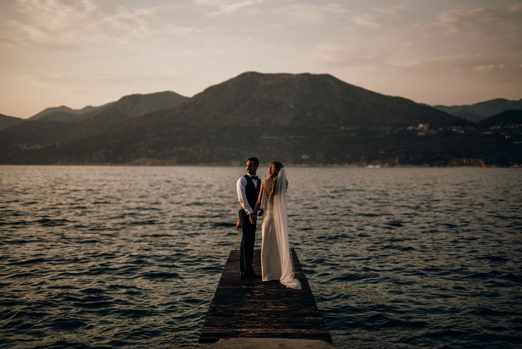 Dubrovnik Kolocep island peer photo at wedding photosession. The couple is looking at the mountains in the background during sunset. The bride is wearing a simple wedding dress. The sea is wavy.