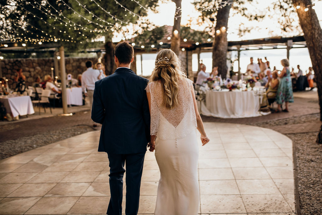 Couple arriving to their wedding reception at Villa Ruza restaurant / wedding venue on Kolocep island off the coast of Dubrovnik. There are string fairy lights and round as well as rectangular tables.