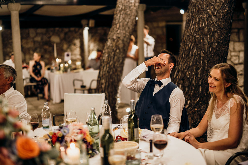 Dubrovnik Kolocep island wedding reception laughter and jokes. During the best man's speech the bride and groom are laughing.