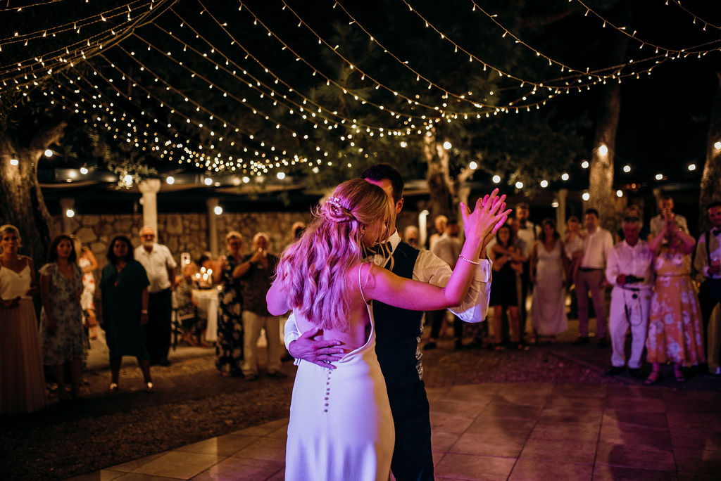 Couple doing their first dance as a married couple at wedding reception on Kolocep island. The fairy lights are on as well as ambiental purple lights. The groom is embracing the bride. The guests are cheering them on in a circle around them.