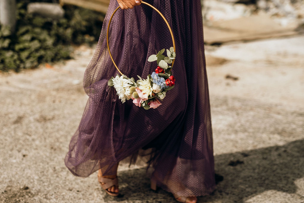 Dubrovnik wedding flowers. A bridesmaid is wearing a purple skirt and carrying a golden circle with wedding florals.