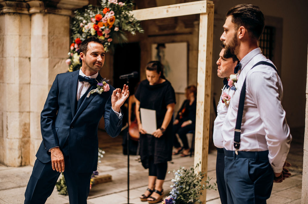Dubrovnik wedding ceremony at Sponza palace. The groom is waiting for the bride in excitement, showing the chef's kiss sign to his best man. He's wearing a stunning navy suit.