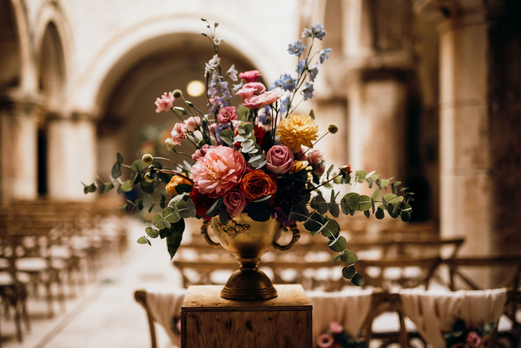 A beautiful flower arrangement for the Sponza palace wedding ceremony. It's in a golden cup and the flowers are colorful. You can see the chairs for the ceremony in the background.