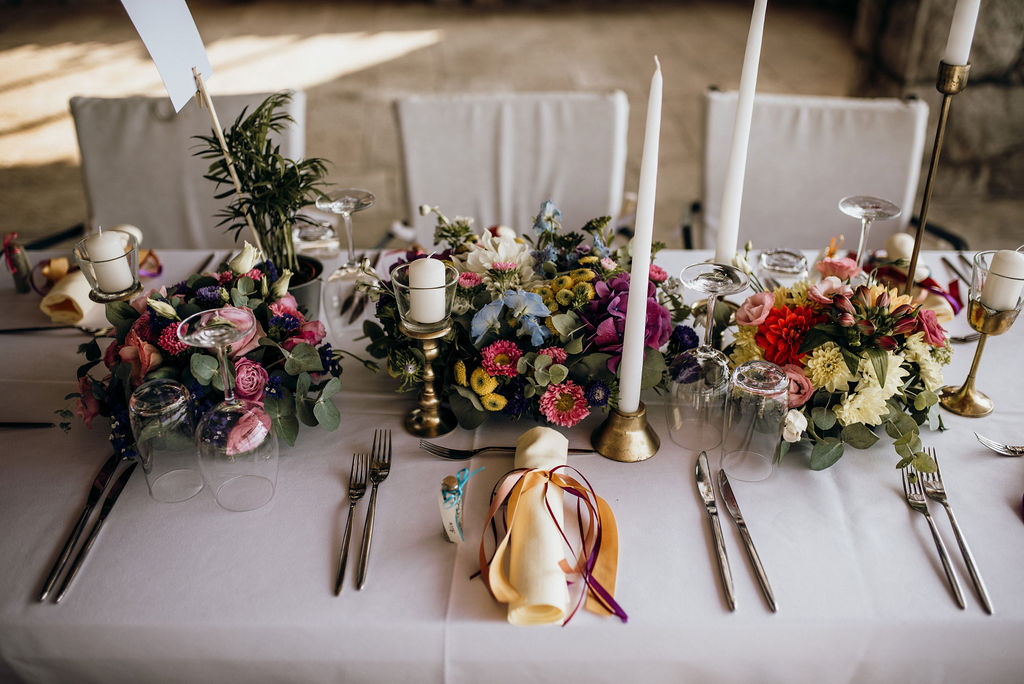 A beautiful wedding reception set up: florals, decoration, rentals. The flowers are colorful and there are simple white tall candles. The linen is yellow and there's a cute little wedding favor.