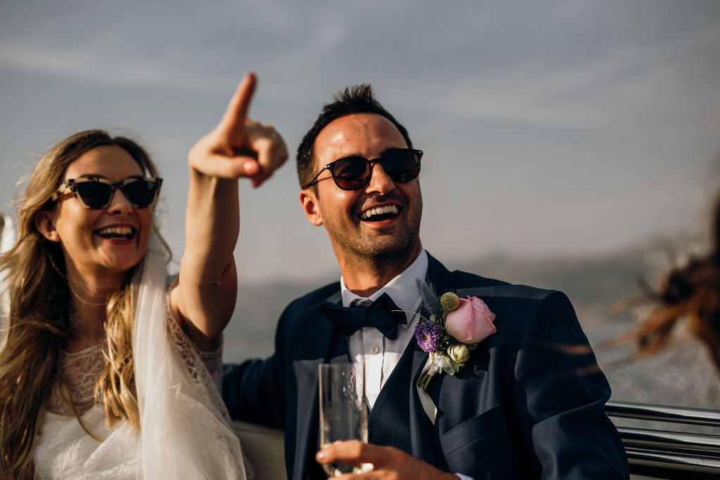 Our beautiful couple arriving to their wedding reception at Villa Ruza on Kolocep island. The bride is pointing to the venue and the guests. The groom is laughing and holding a champagne glass.