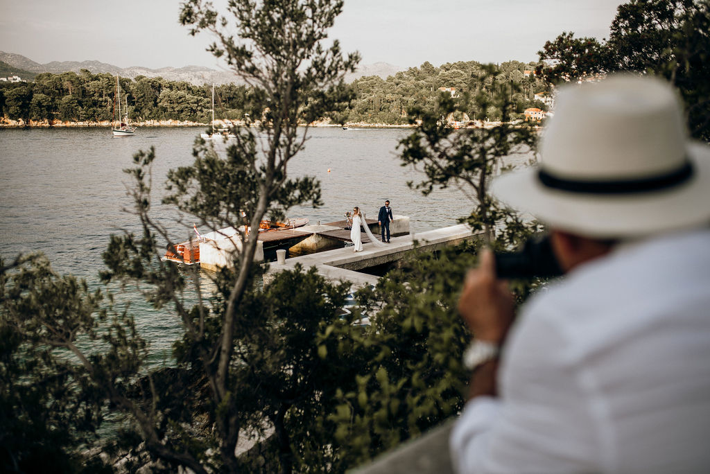 Romantic arrival to Villa Ruza on island Kolocep. We can see one person taking a photo, but in focus is the couple who just got off the boat. They are on a beautiful peer and we can see the island in the background.