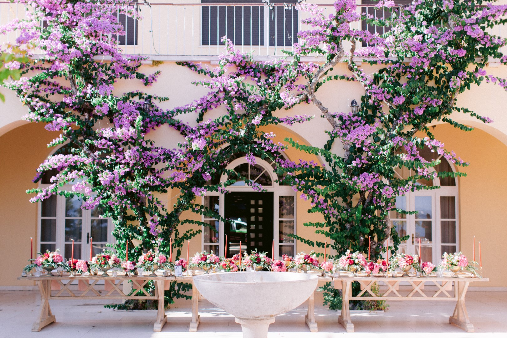 Split Villa Dalmacija wedding reception set up. On this photo is a big rectangular table set up and behind it a huge bougenvilia plant on the wall. The flower arrangements and candles are pink.