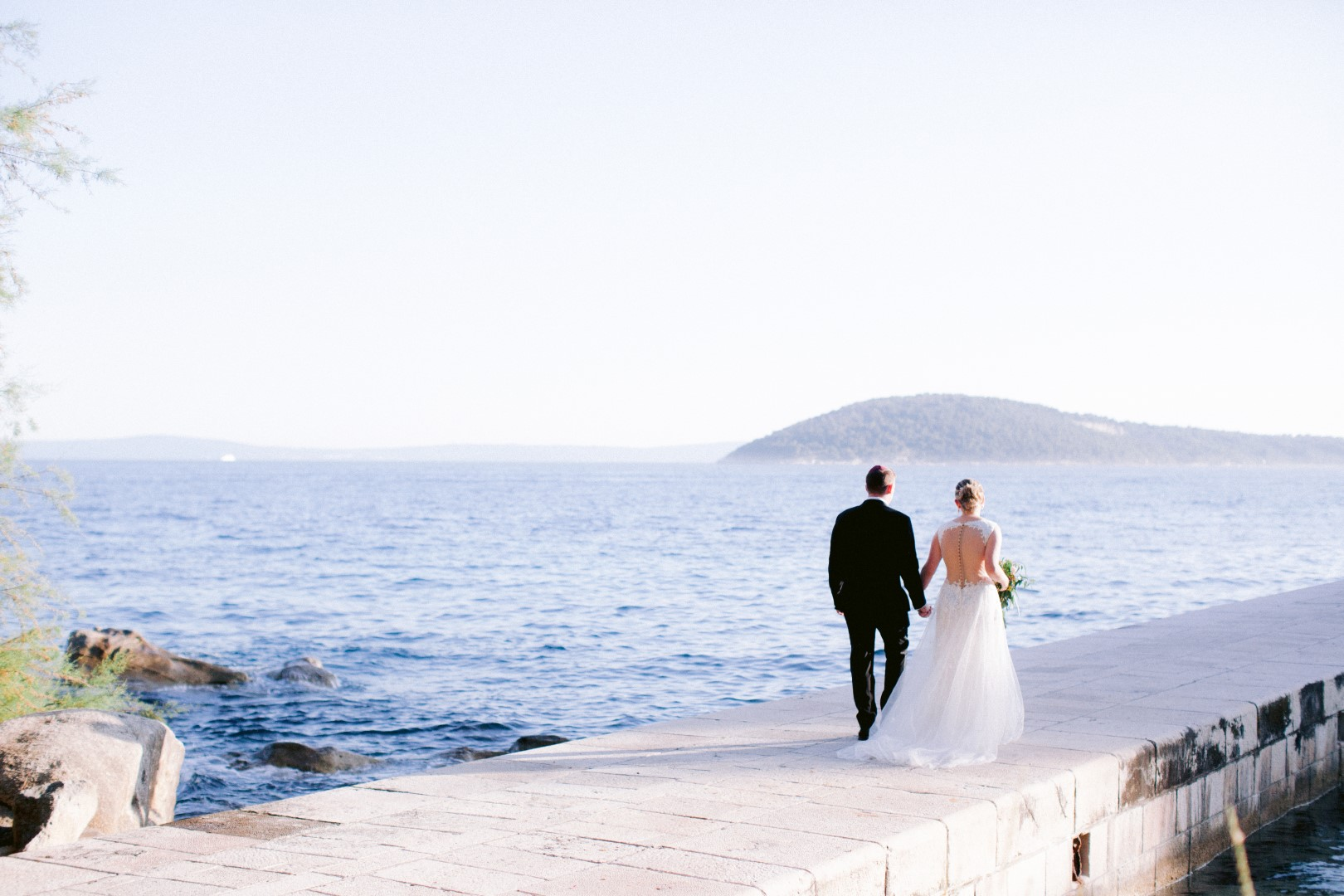 Split destination wedding bride and groom. They are holding hands and walking down the peer at Villa Dalmacija. We can see their backs and a mountain in the background.