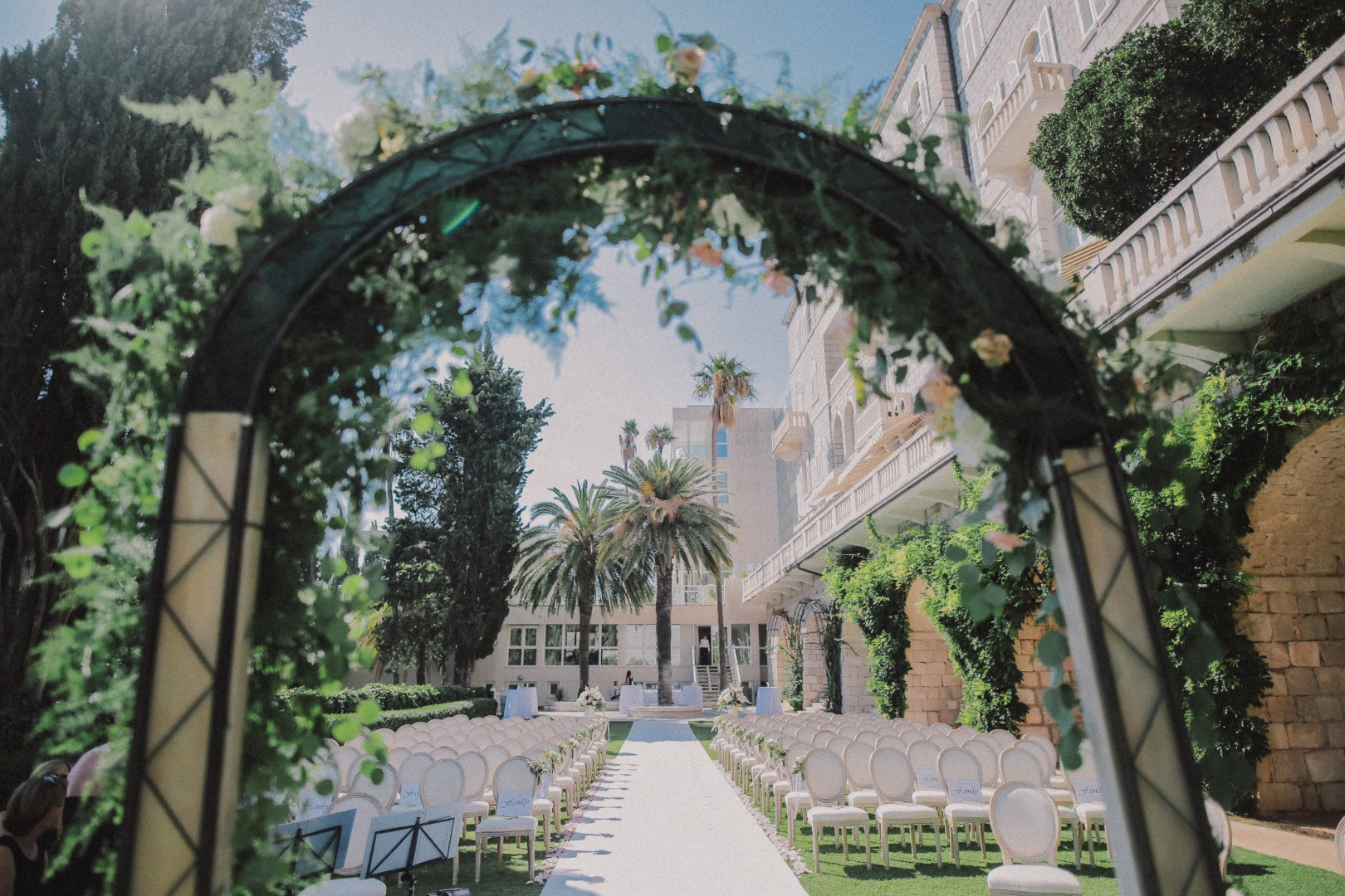 This photo shows the behind of an arch set up for a wedding ceremony. It is a garden ceremony in front of the Villa Argentina hotel in Dubrovnik. There are many beautiful white chairs and palm trees in the background.