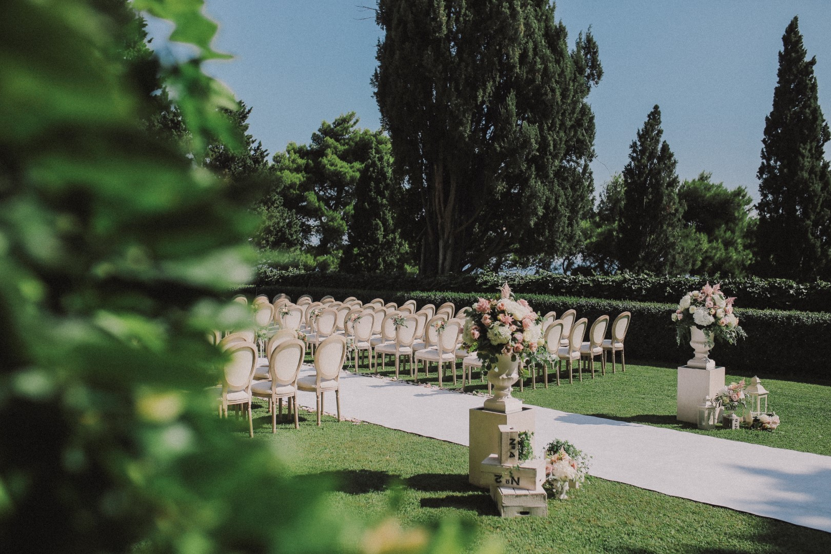 This is a beautiful garden ceremony in Dubrovnik. There is a white carpet and white Louis chairs. Behind the chairs are flower arrangements with a white and pink color theme.