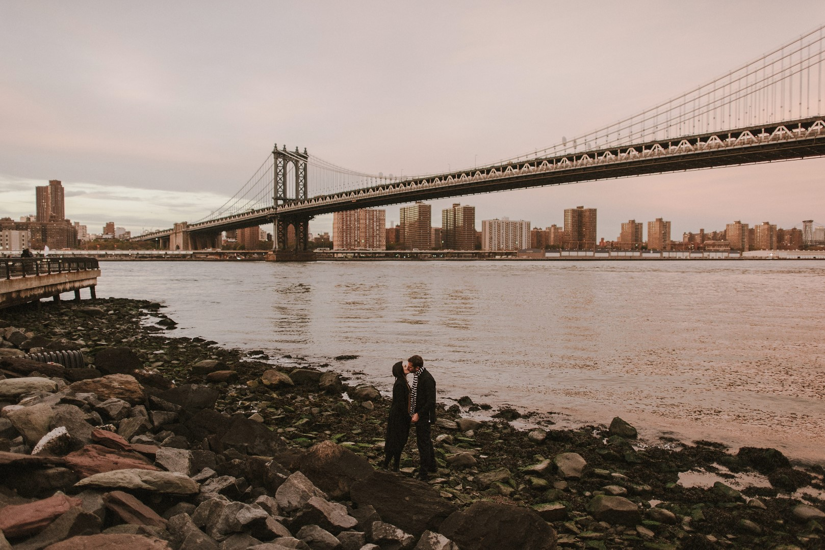 A photo from the New York Wedding Photosession by Marko Marinkovic. The couple is from New York. In the background is the bridge and they are on the shore kissing.