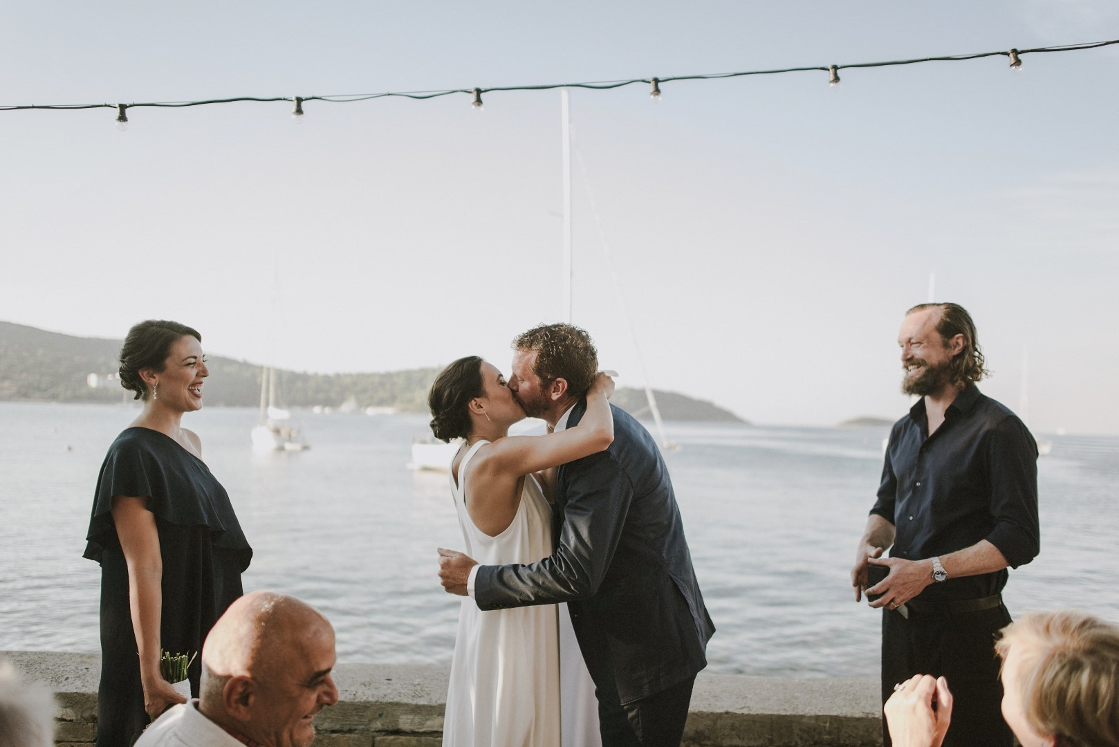 Vis island wedding ceremony. In the background we see the sea and mountains. The best man and maid of honour are laughing while the couple is kissing.