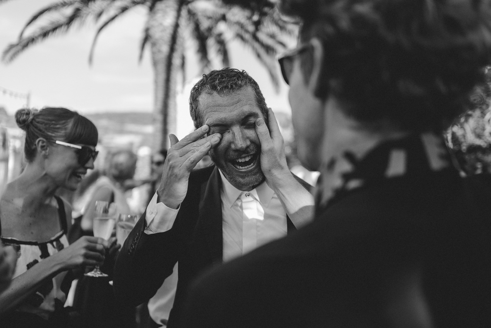 This photo is black and white, taken by Marko Marinkovic. The groom is crying happy tears after the ceremony. One of the guests is wiping off his tears and they are laughing.