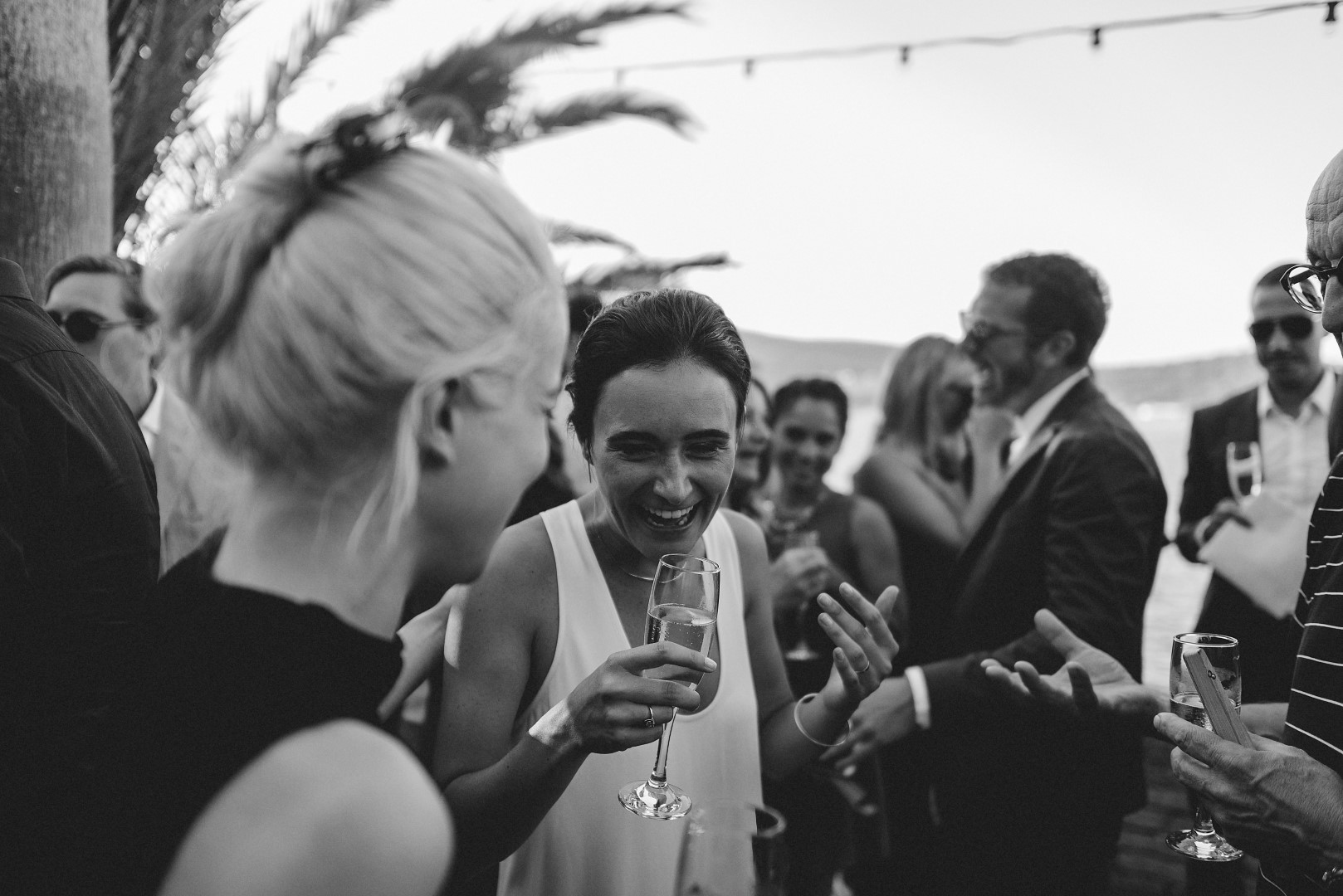 The photo is black and white, taken by Marko Marinkovic. In the focus we have the bride holding a champagne glass and laughing. In the background is the groom laughing with the guests.