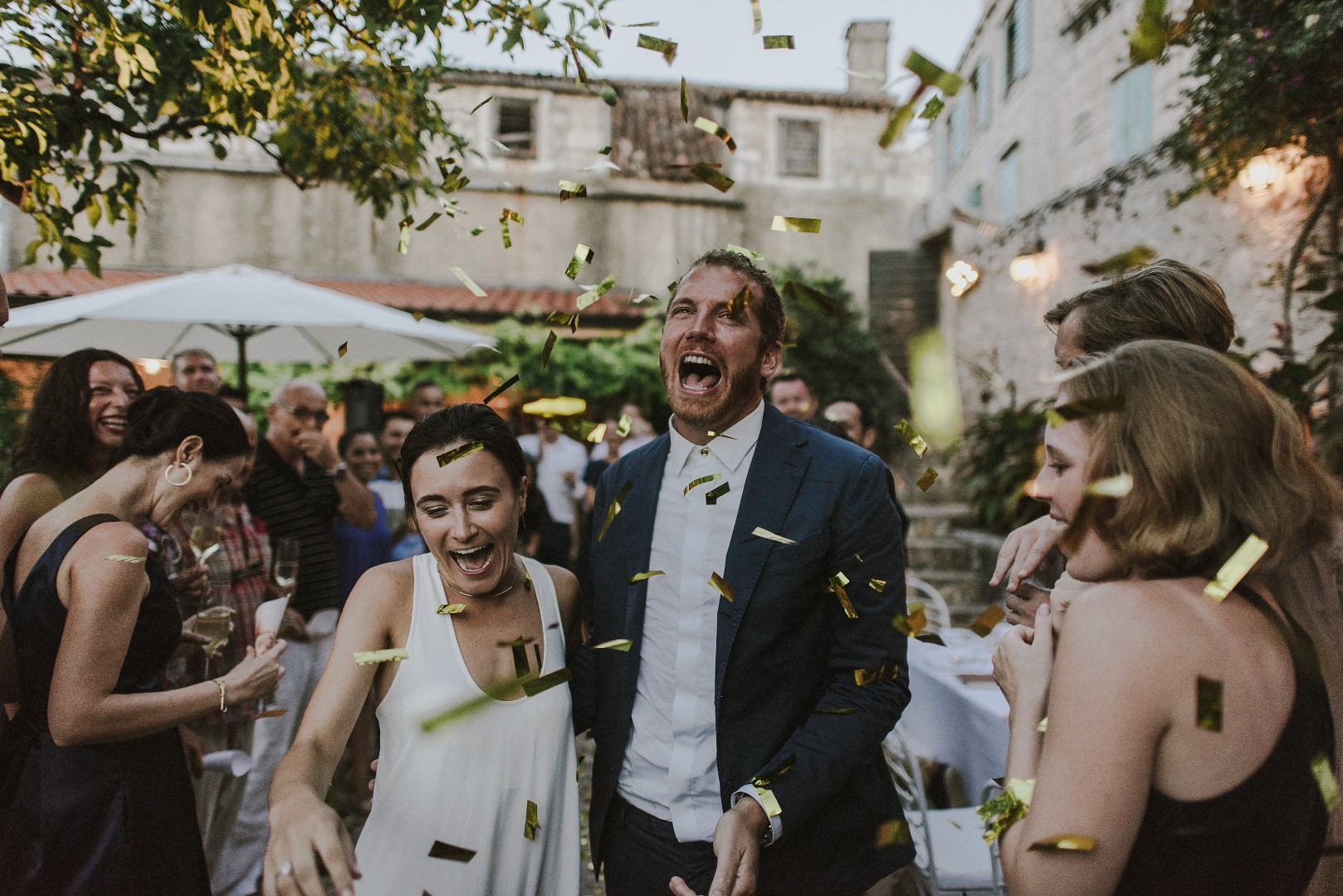 This is a photo of the happy couple arriving to the reception. There are golden confetti flying around everywhere and the guests around them are laughing. The groom is wearing a stylish navy suit while the bride has an updo and a simple white dress.