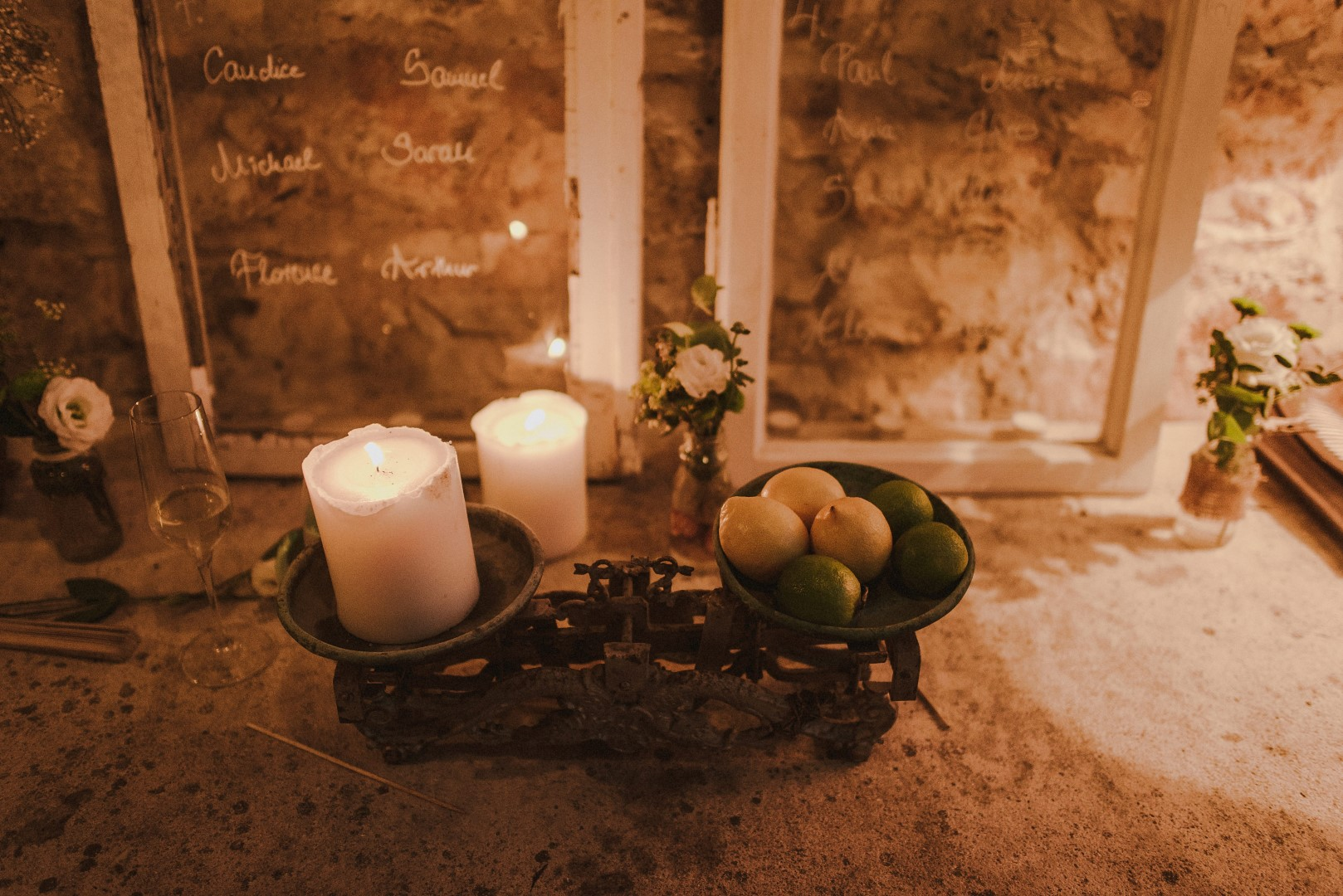 This is a photo of some details from the wedding reception. It is now dark so the candles have been lit. On the side of the candles are some citrus fruits and behind are two mirrors with white writing on them. These are the names of the guests.
