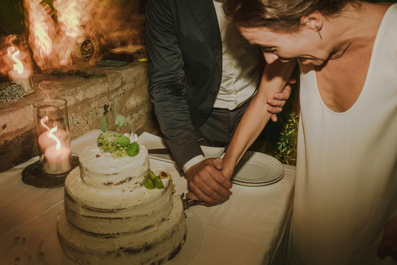 Photo of cake cutting. The groom is holding the bride's hand and they are cutting together. The cake is white, looks unfinished on purpose and there are green figs on it.