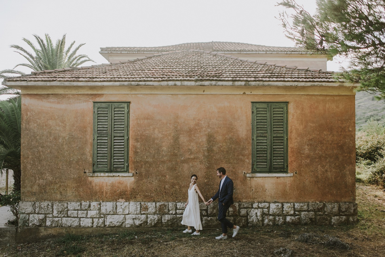 A photo of the happy couple from their photosession with Marko Marinkovic. Behind them is a small house with lovely green windows. They are holding hands and smiling at each other.