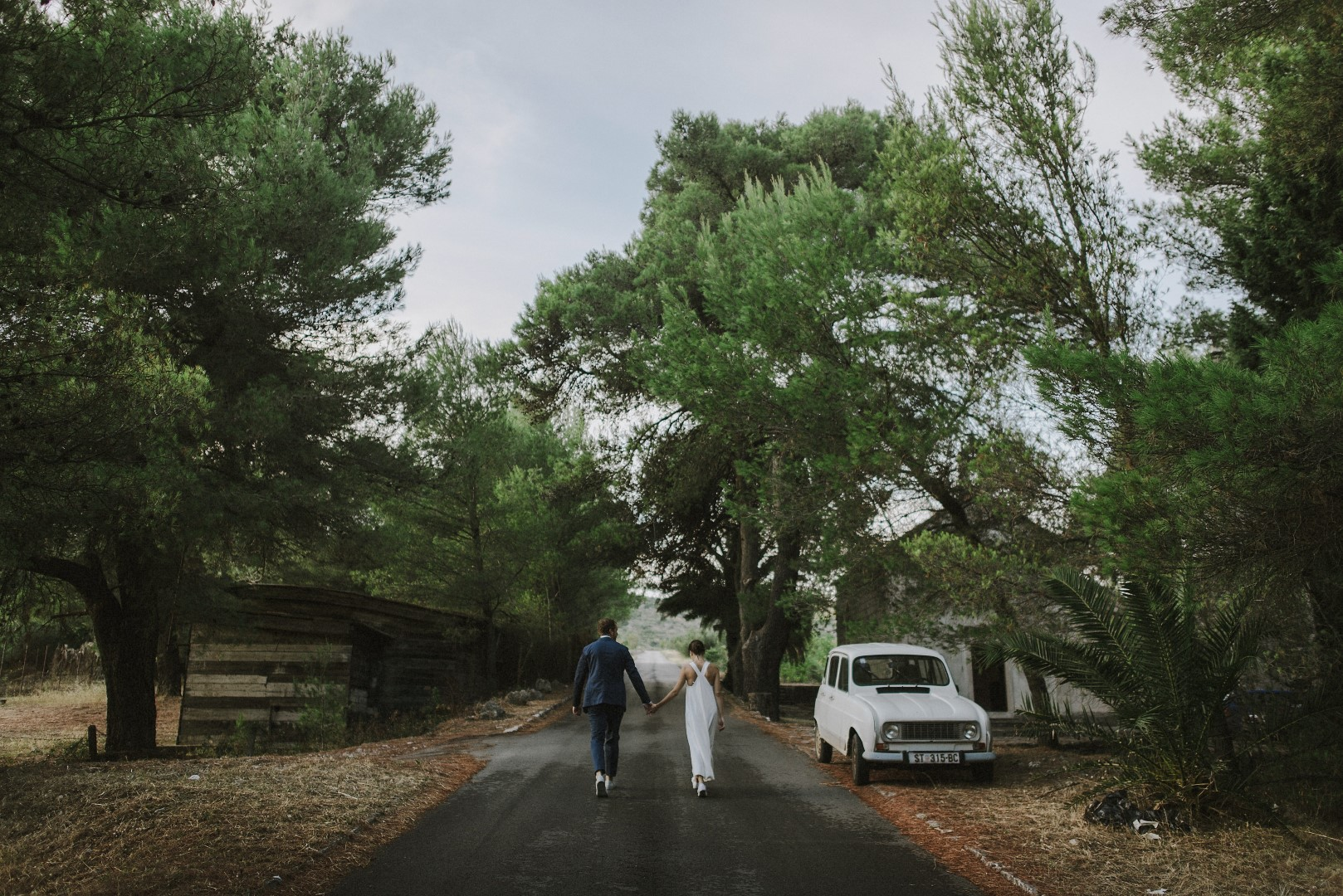 A photo of the happy couple from their photosession with Marko Marinkovic. We can see them from behind as they are holding hands. They are on an empty road, a white old fashioned car next to them and beautiful trees all around.