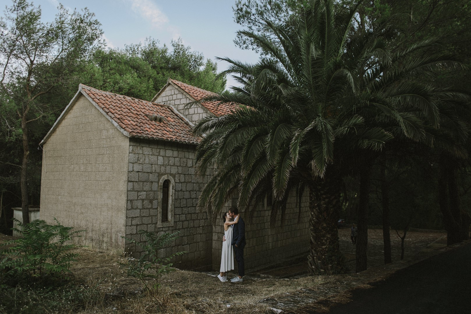 A photo of the happy couple from their photosession with Marko Marinkovic. Behind them is a church with stone walls as well as some palm trees. They are embracing each other and kissing.