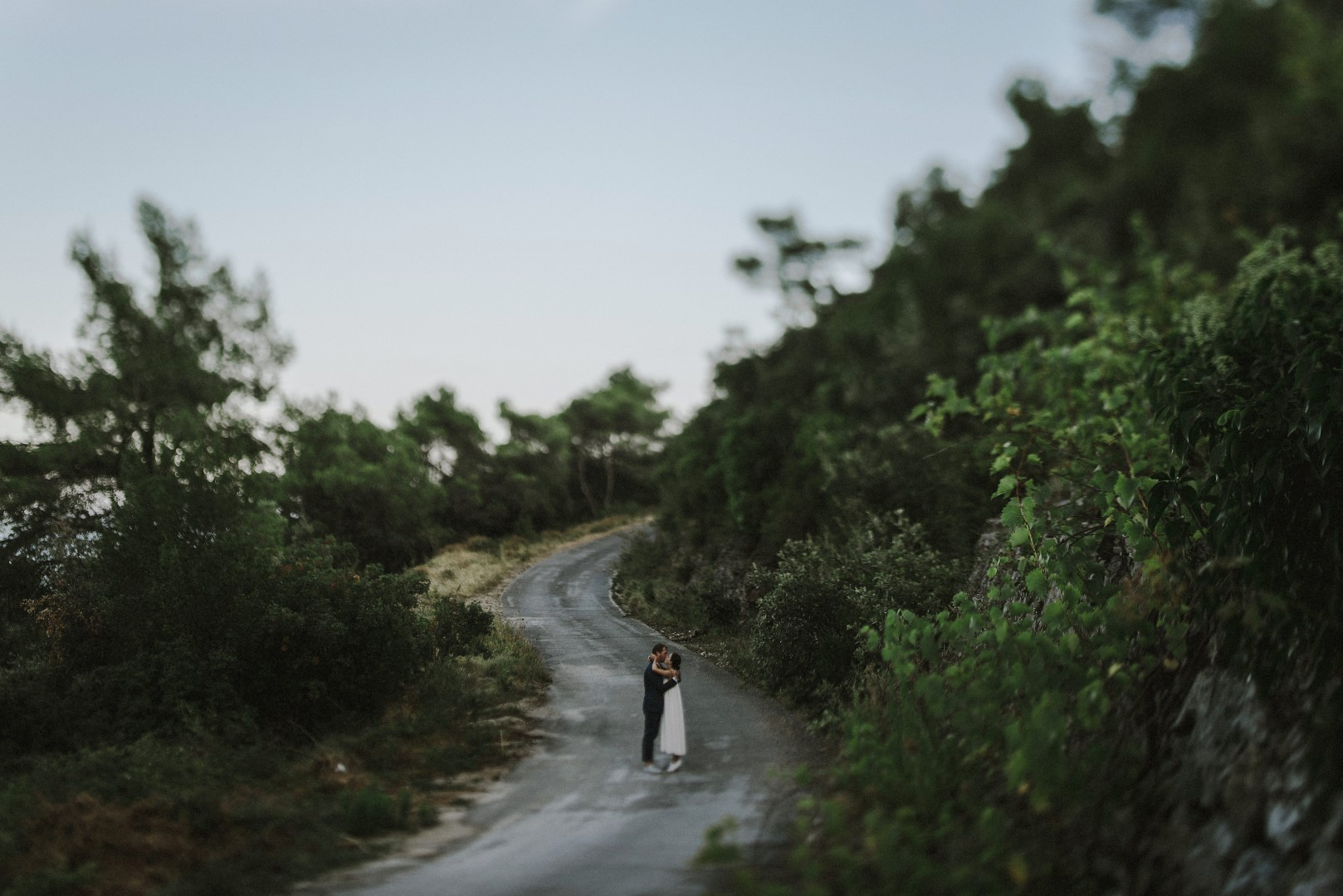 A photo of the happy couple from their photosession with Marko Marinkovic. They are on an empty, winding road. Around the road is a lot of greenery and the couple is kissing.