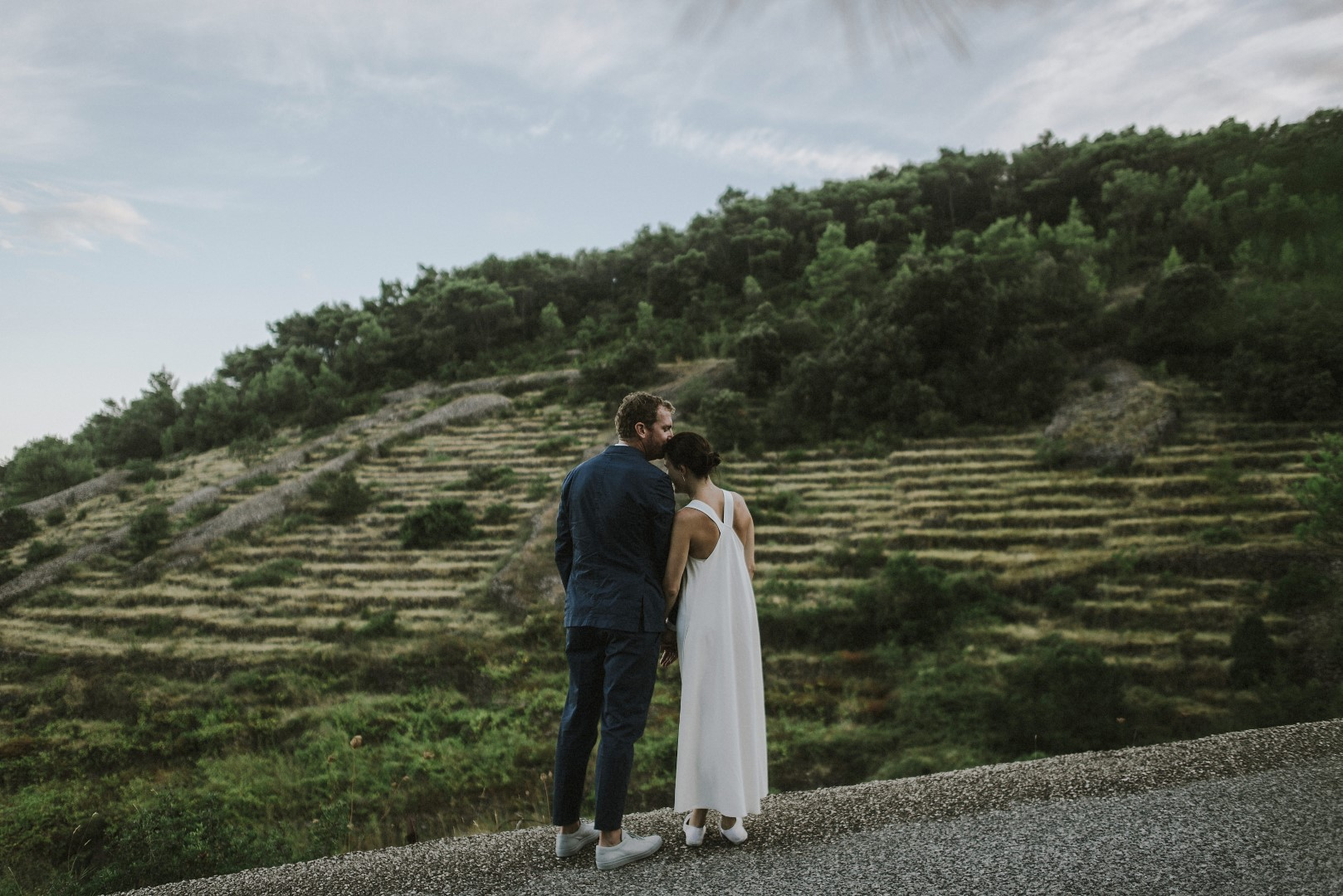 A photo of the happy couple from their photosession with Marko Marinkovic. We can see them from behind as them groom is giving the bride a kiss on the head. In front of them is a stunning mountainous vineyard.