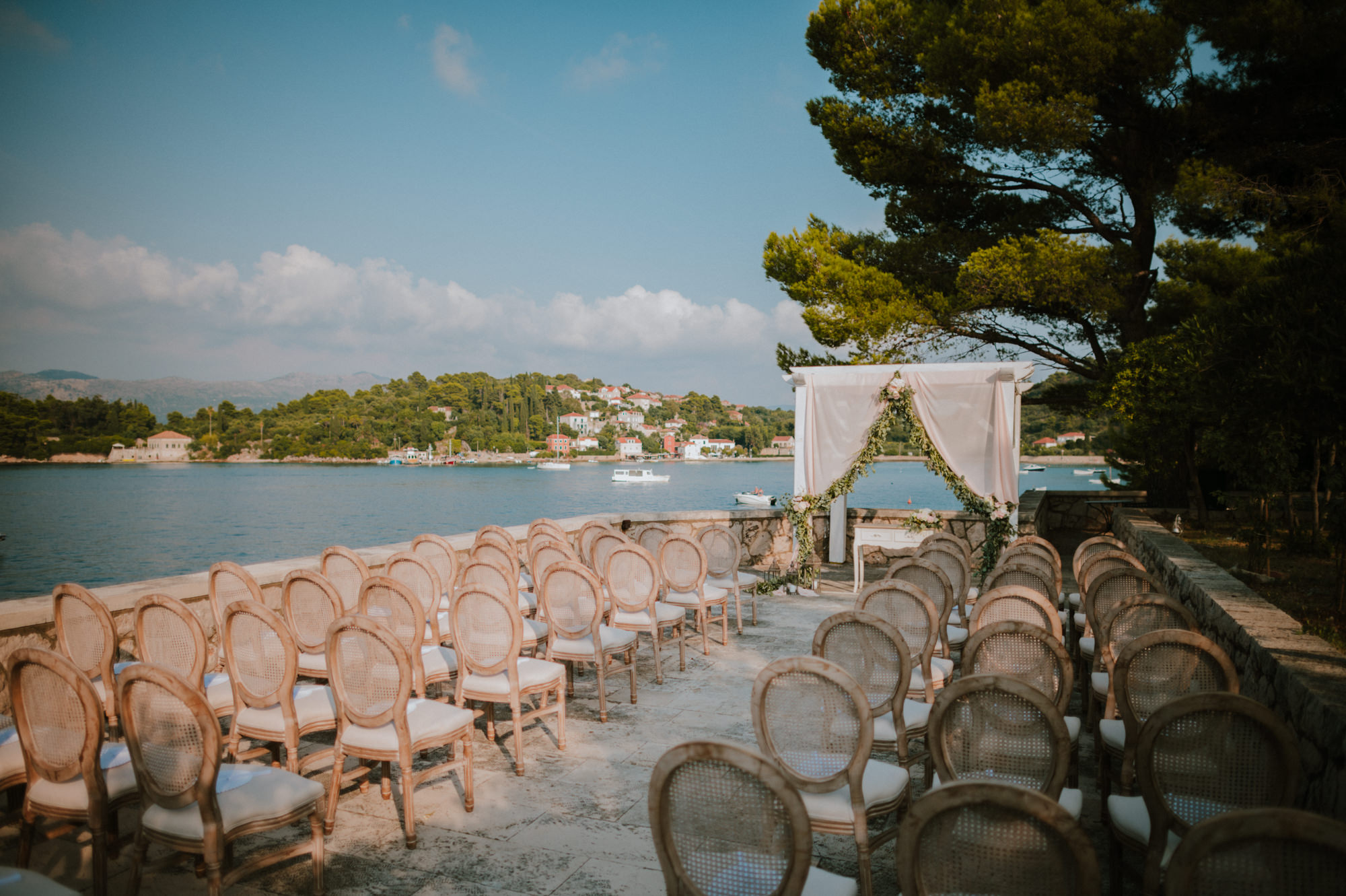 An image of a ceremony set up at Villa Ruza restaurant on Kolocep island off the coast of Dubrovnik. Louis chairs, an arch and a white curtain with greenery on it.