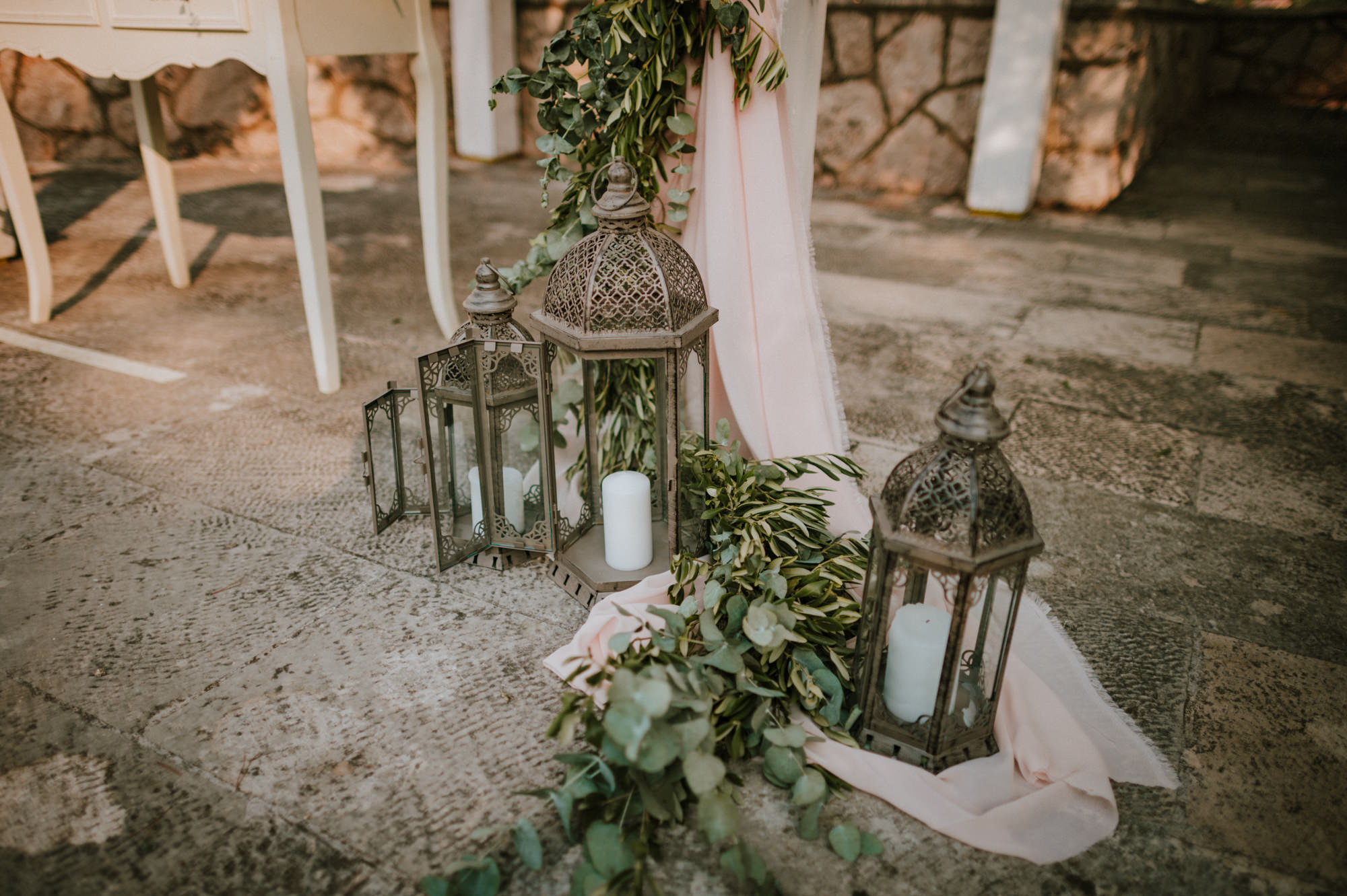An image of a ceremony set up at Villa Ruza restaurant on Kolocep island off the coast of Dubrovnik. Louis chairs, an arch and a white curtain with greenery on it. We can also see bird cages and pink roses.