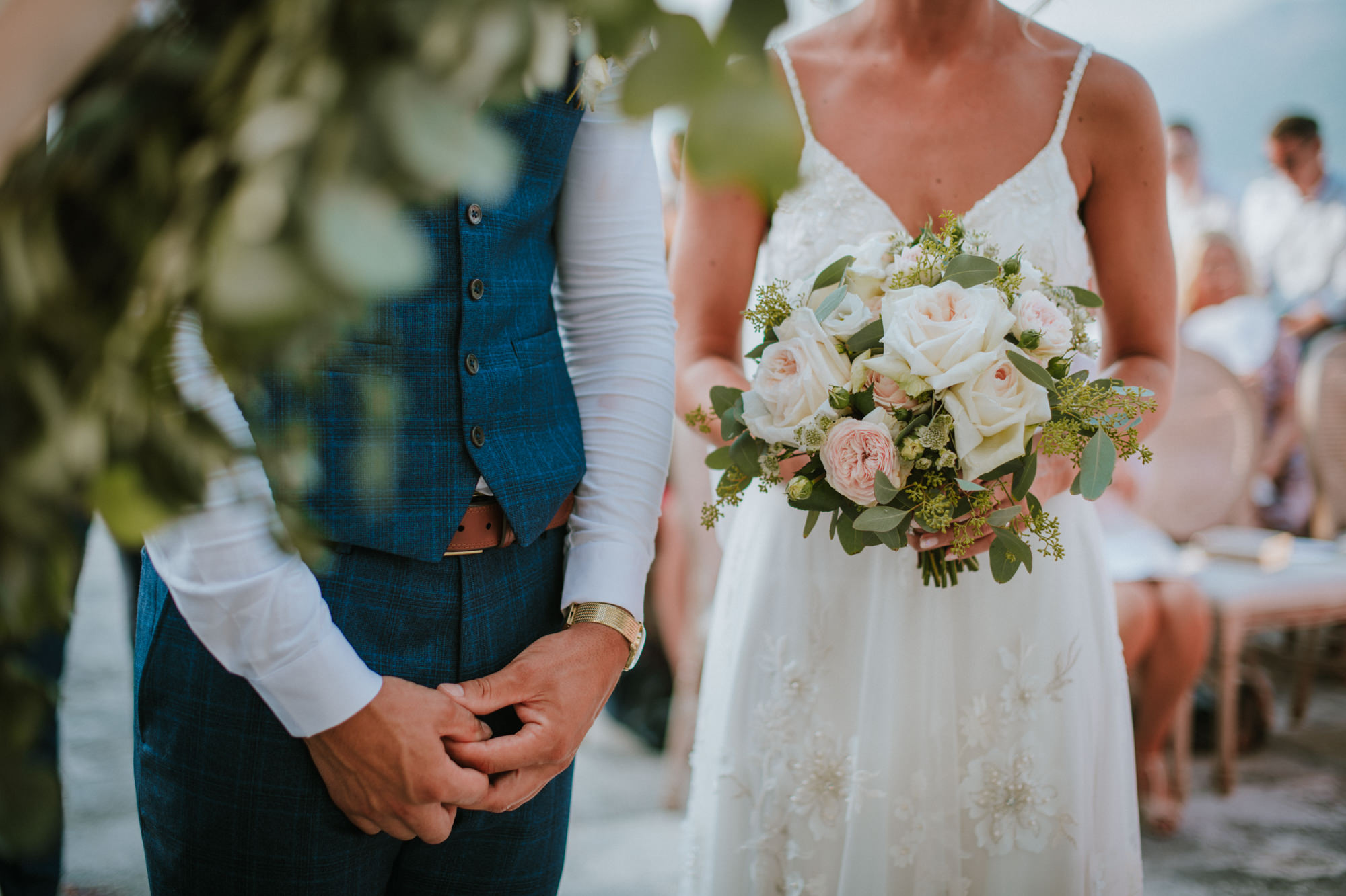 A close up image of the wedding couple on which we can't see their faces, but we can see that he is wearing a lovely navy suit with a vest and she has a simple sparkly wedding dress. She's holding her wedding bouquet of blush pink roses.