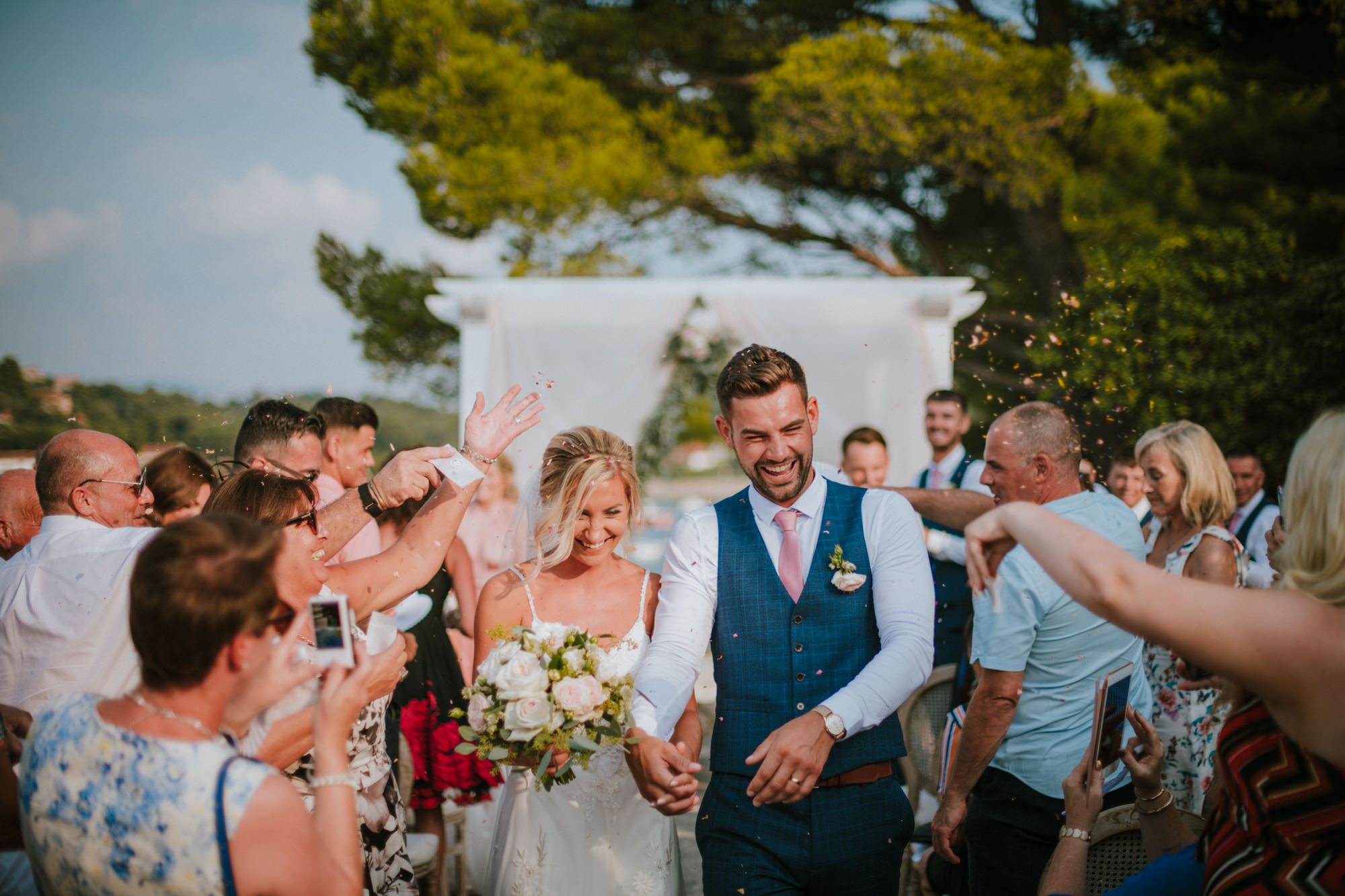 This image shows the couple just after they got married and finished the ceremony, they are laughing as they are passing through the guests who are throwing confetti on them.