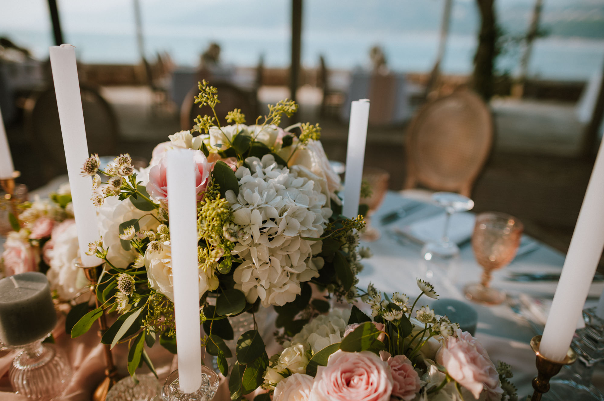 This image is a close up of the reception table set up. The flower arrangements are a mix of white and blush pink roses. The glasses are rose gold and there are also tall white candles on the table.