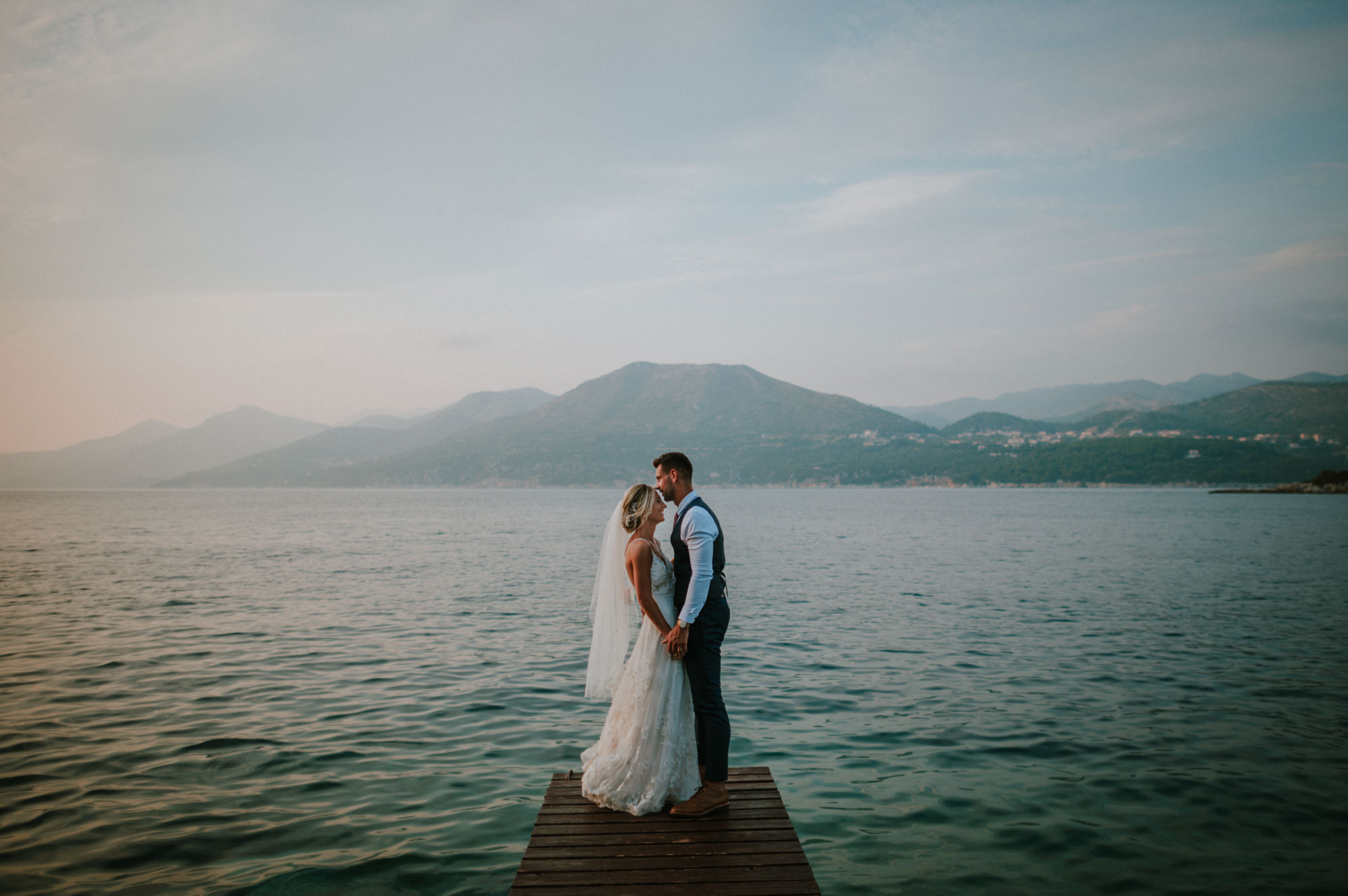 This photo shows a couple on their photoshoot on a peer under Villa Rose restaurant on Kolocep island. In the background is the sea and mountains.