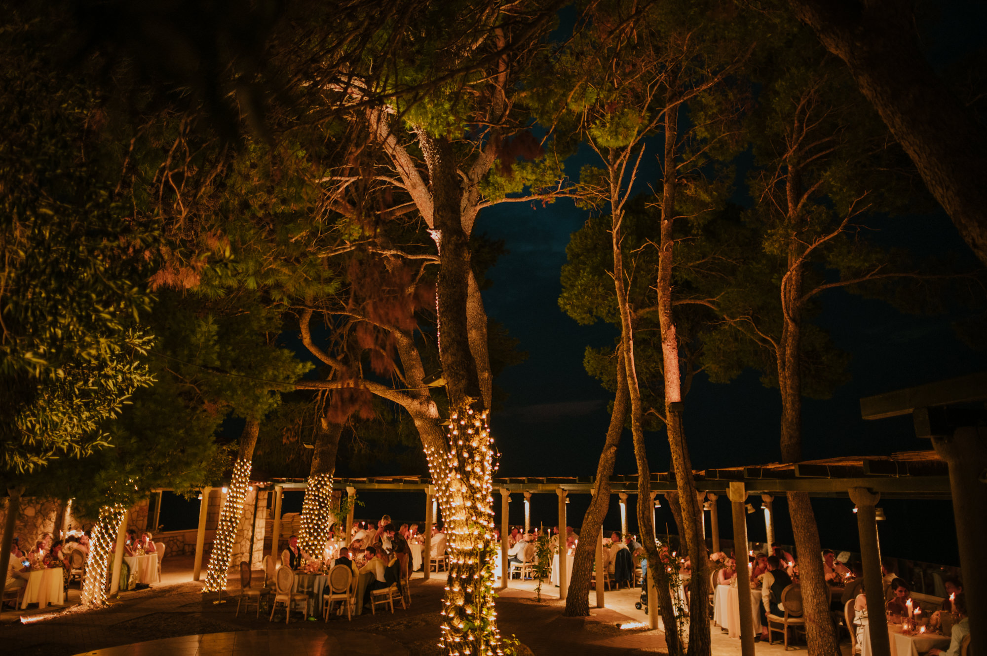 This photo shows Villa Rose restaurant on Kolocep island in the evening ready for a wedding reception. There are string lights on the trees and tables all around.