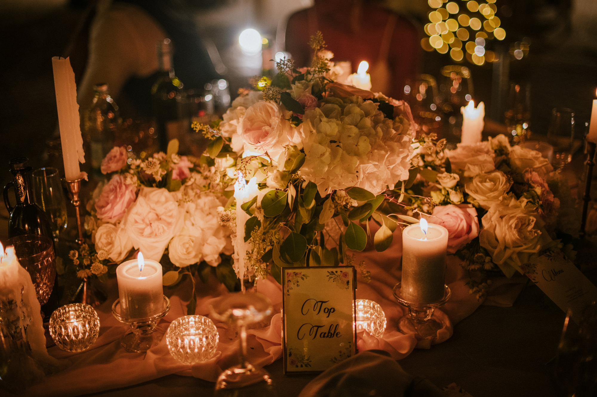This is a top table for the wedding reception. There is a sign that says top table on it. The flowers are white and pink. There are small white candles and crystal cups.