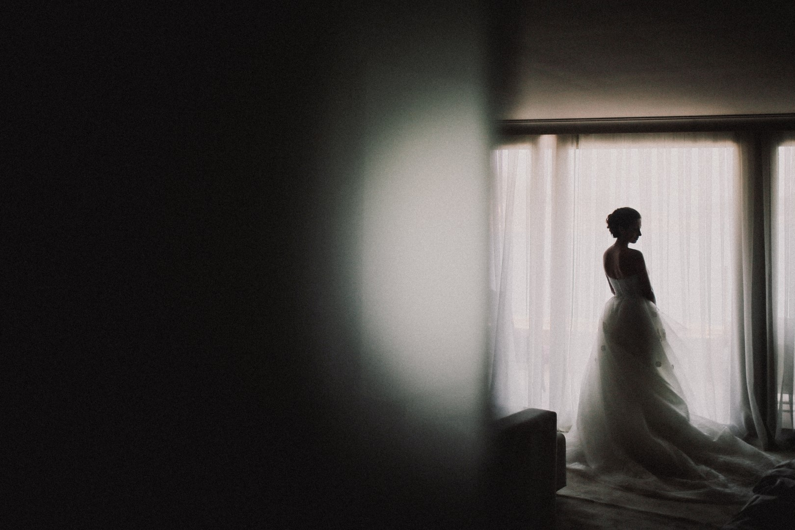 This is a photo of the bride. There isn't much color and it's blurry, very atmospheric. She just got ready in the hotel. We can see her back. She is in front of a window and wearing a beautiful long white wedding dress.