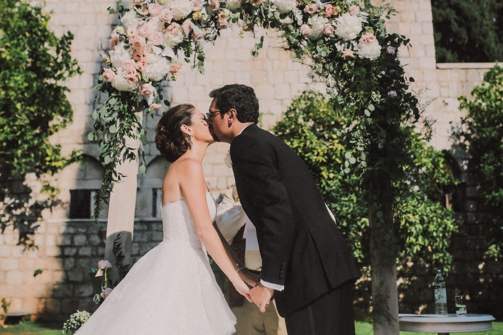 The happy couple just got married. They are beneath a white and pink greenery-flower arch. They are giving each other the first kiss as husband and wife.