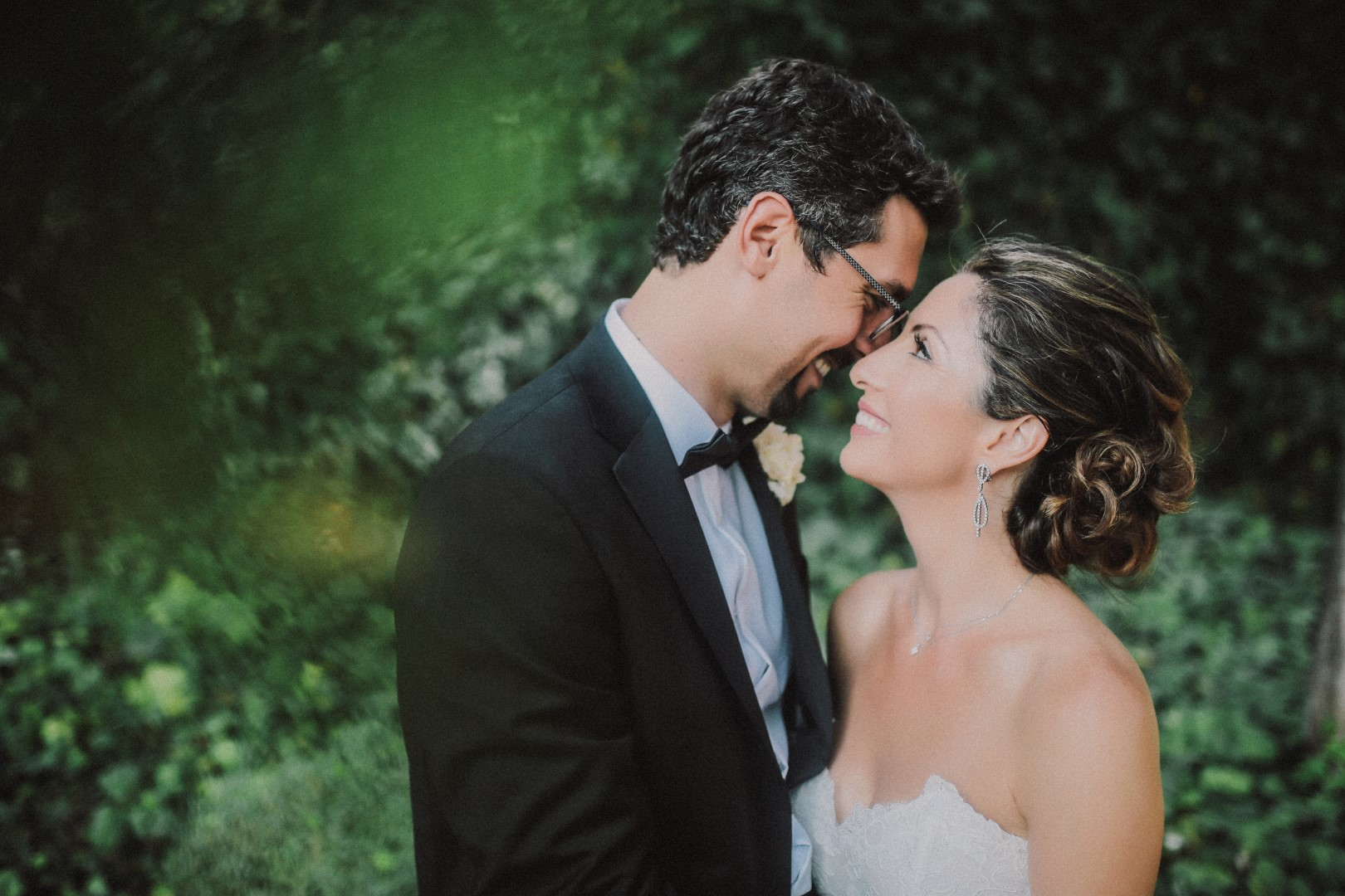 This is a photo from the photosession of the happy couple. They are in a garden. They are looking at each other. She has a beautiful updo.