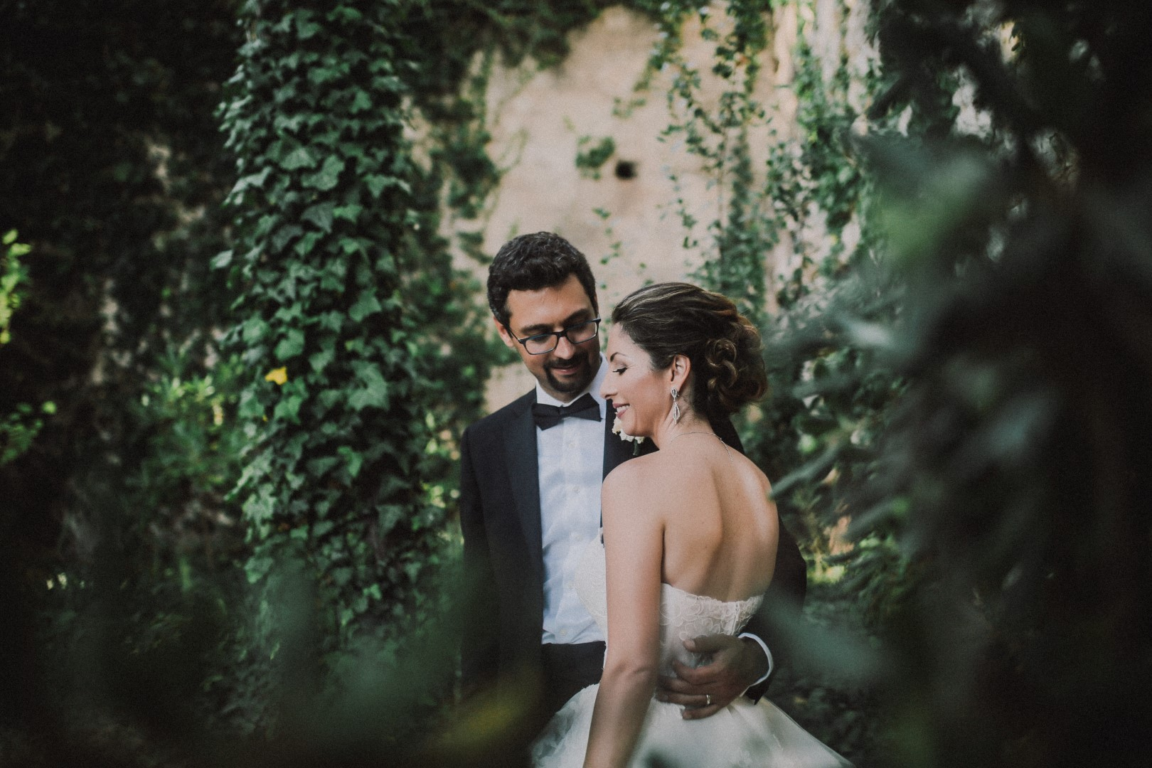 This is a photo from the photosession of the happy couple. They are in a garden. The groom is giving her a hug. She has a beautiful updo.