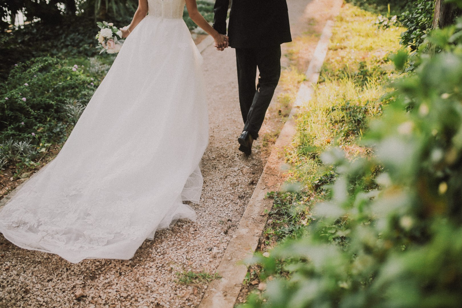 This is a photo from the photosession of the happy couple. They are in a garden. You can only see their legs, her beautiful long dress and his black suit.