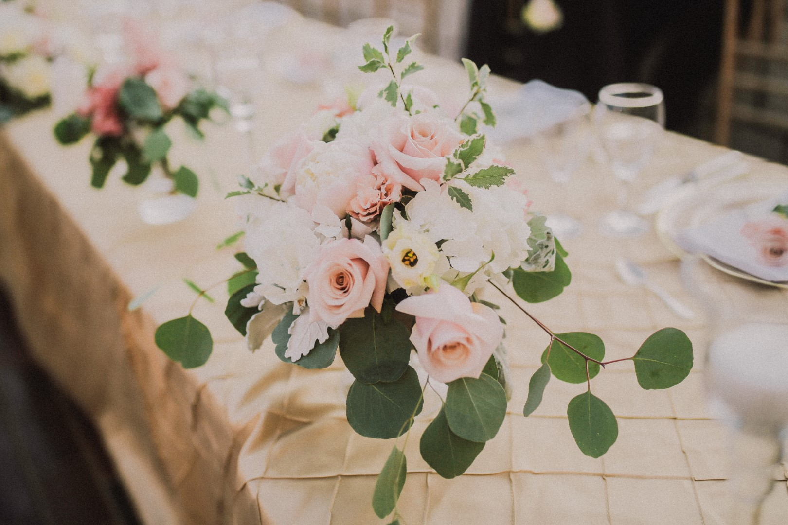 This is a close up of the wedding reception table. The tablecloth is blush as well as the flowers. Some of the flowers are white. There are plates and glasses in the back.