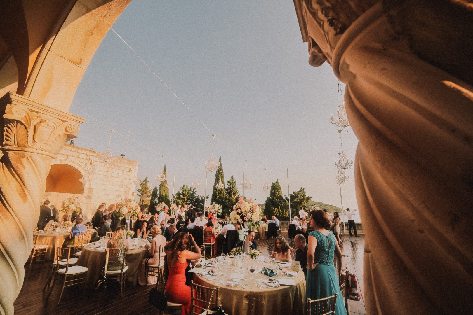 This is a photo of the wedding reception on the Art gallery terrace in Dubrovnik. The camera is behind the collumns and facing the round tables with guests. They are waiting for the couple to arrive. Some are sitting and some are standing. There are chandeliers above them.